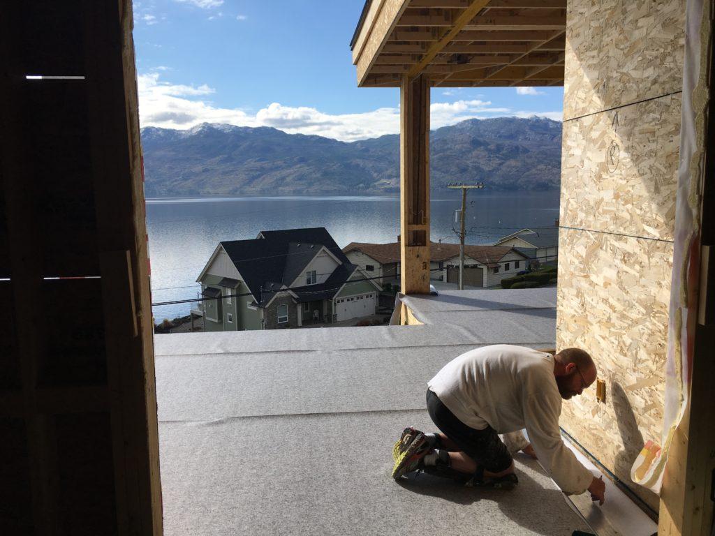 Man installing waterproof Vinyl decking during new home construction