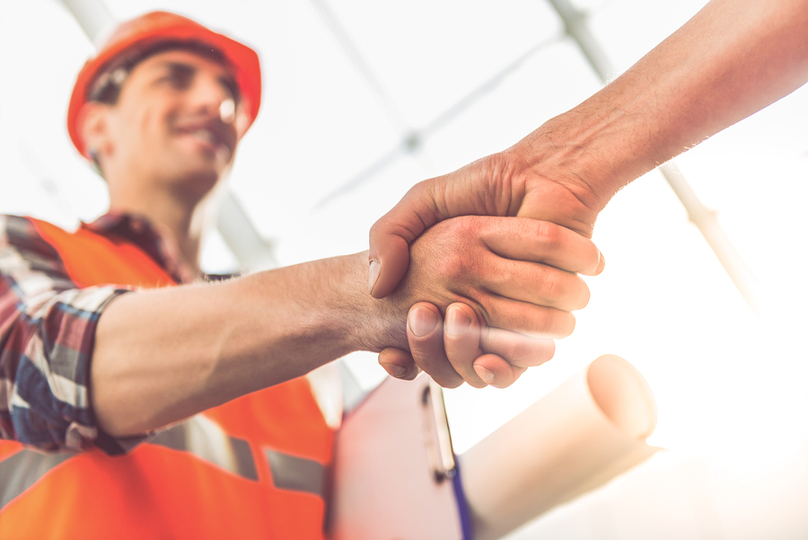 Construction contractor holding plans and shaking hands with someone - Econodek